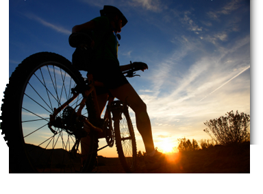Image of sunrise and mountain bike cyclist silhouette on nature ride with cirrus clouds in the blue and orange sky. It's time to get out there and enjoy Austin on a bicycle!